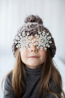 Drôle petite fille avec des flocons de neige comme yeux