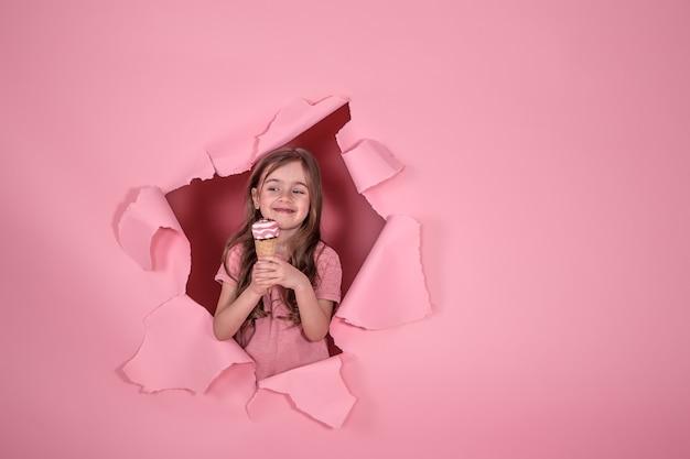 Drôle de petite fille avec de la glace sur fond coloré