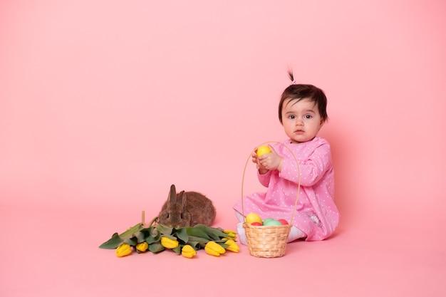 Drôle de petite fille avec lapin, tulipes, panier avec des oeufs colorés.