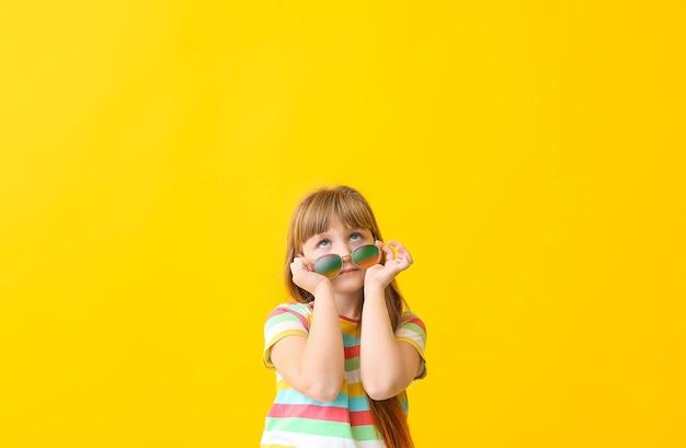 Drôle de petite fille avec des lunettes de soleil sur la couleur