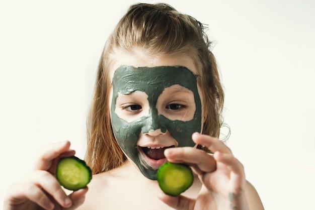 Drôle petite fille avec un masque cosmétique d'argile dans une serviette de bain
