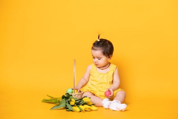 Drôle de petite fille mignonne en robe jaune avec des tulipes, panier avec des oeufs colorés.