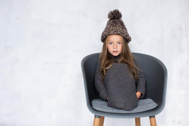 Drôle petite fille portant un chapeau d'hiver