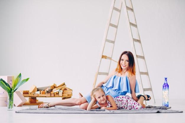 Drôle petite fille s'amuser avec sa maman dans la salle décorée en blanc. espace de copie vide, espace libre pour le texte.