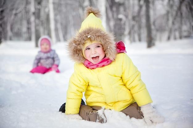 Drôle petite fille en vêtements d'hiver dans une forêt enneigée