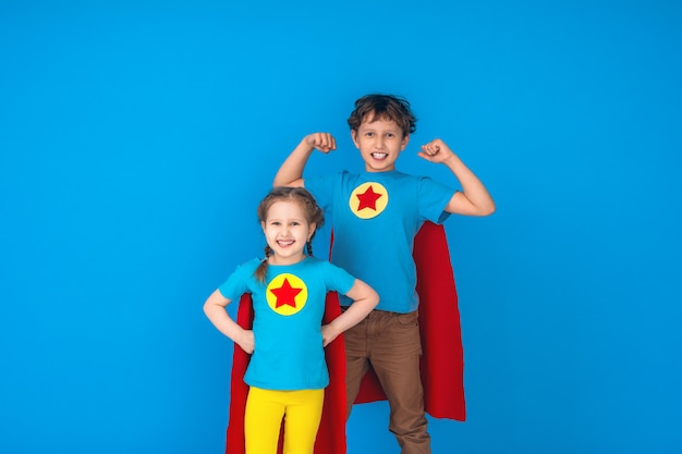 Drôle de puissance de super héros de petits enfants en imperméables rouges et masque.