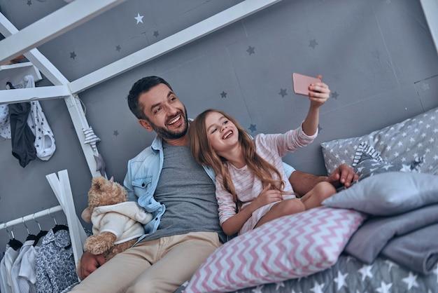 Drôle de selfie! joyeux père et sa petite fille prenant un selfie assis sur le lit à la maison