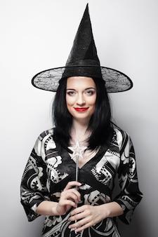 Drôle de sorcière. jeune femme heureuse avec chapeau de canival. prise de vue en studio.