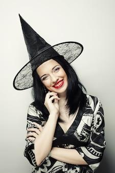 Drôle de sorcière. jeune femme heureuse avec chapeau canival.
