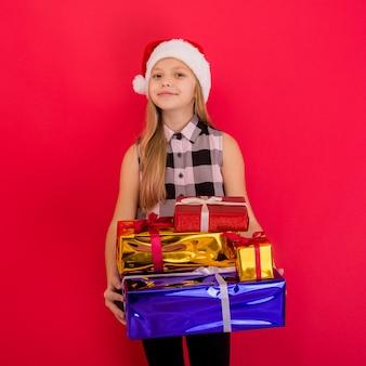 Drôle souriant joyeux enfant fille en bonnet de noel tenant le cadeau de noël à la main sur le fond rouge - image