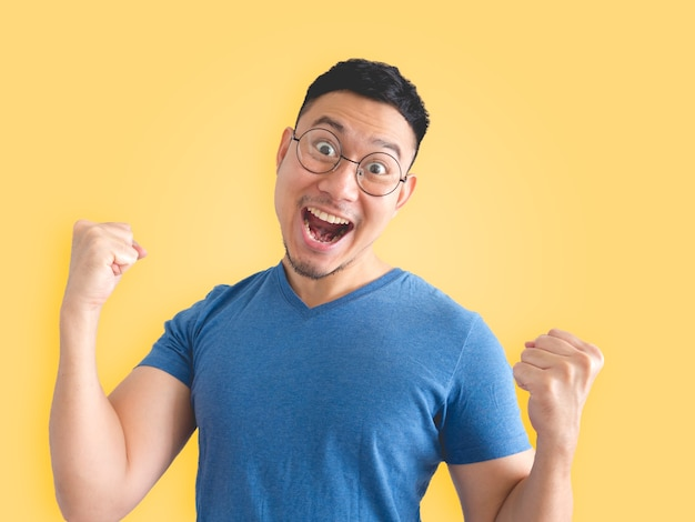 Drôle de surprise et de joie de l'homme asiatique en t-shirt bleu et des lunettes.