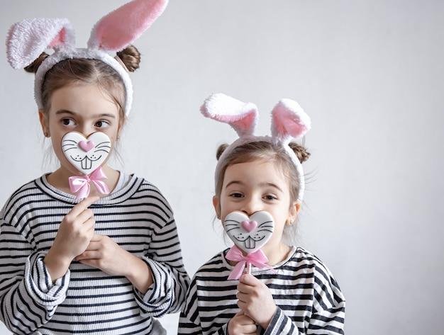 Drôles de petites filles avec des oreilles de pâques sur la tête et du pain d'épice de pâques sur des bâtons