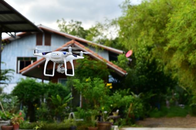 Un drone d'avion décolle de terre et vole pour prendre une photo aérienne devant sa maison