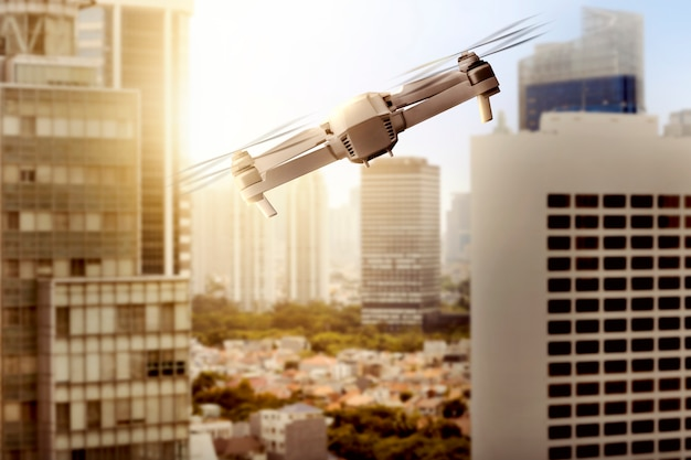 Drone blanc avec caméra volant au-dessus de la ville moderne avec des gratte-ciels