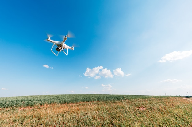 Le drone blanc dans les mains chez l'homme isolé sur fond de champ vert