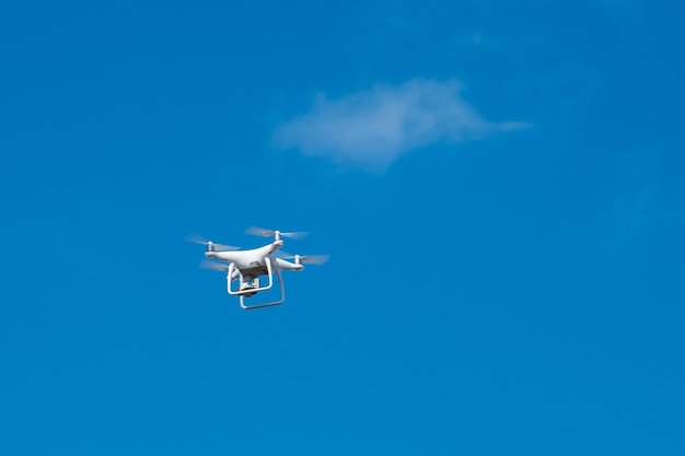 Drone blanc planant dans un ciel bleu vif, hélicoptère radiocommandé avec caméra.