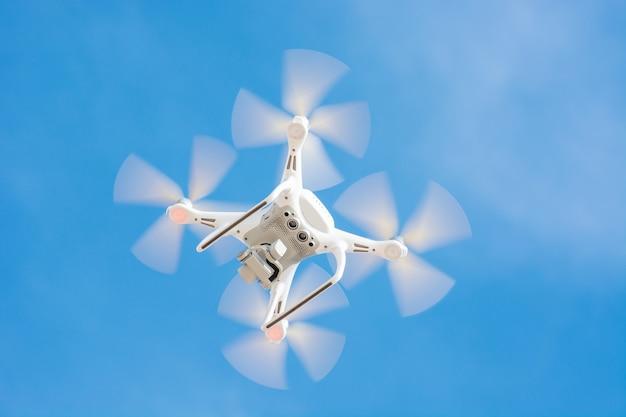 Drone de couleur blanche volant dans le ciel bleu, concept video technology.