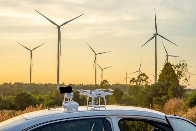 Drone et fond de crépuscule à distance est une éolienne.