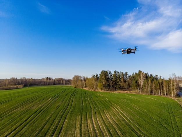 Drone inspectant les champs agricoles verts au printemps avec une végétation fraîche