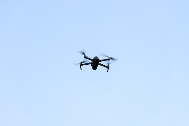 Drone quad copter volant avec ciel bleu.