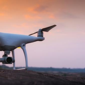 Drone quad hélicoptère avec appareil photo numérique au coucher du soleil prêt à voler pour la surveillance