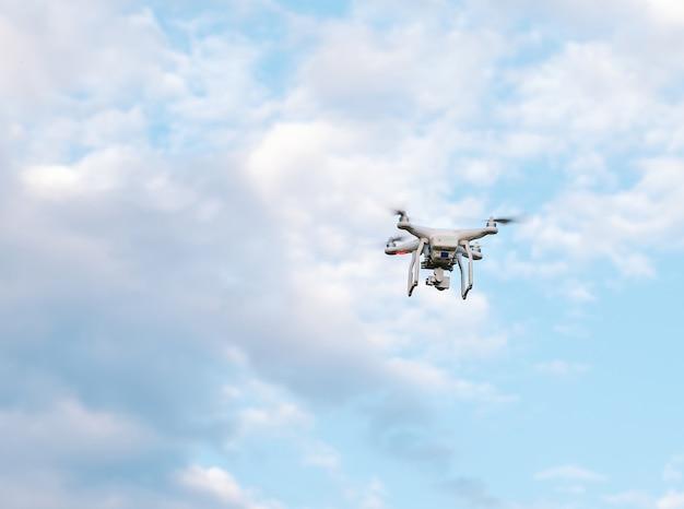 Drone quadcopter avec l'appareil photo contre le ciel bleu