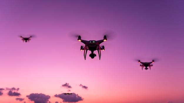 Drone quadcopter avec appareil photo numérique volant au coucher du soleil en soirée belle lumière