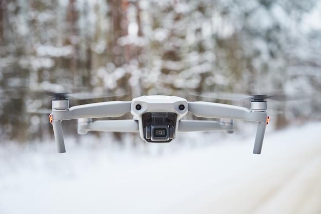 Drone quadcopter avec caméra volant dans la forêt d'hiver