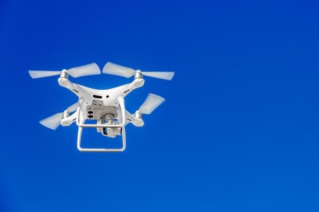 Drone quadricoptère avec la caméra contre le ciel bleu