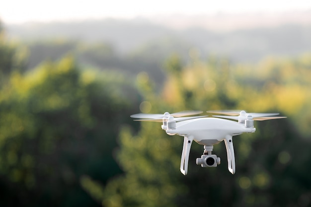 Drone quadricoptère volant avec une caméra au-dessus d'un lac.