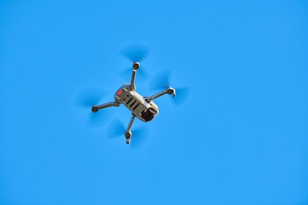 Drone quadrirotor dans le ciel. un petit drone vole dans le ciel en prenant des vidéos et des photos. livraison d'air télécommandée et espion.