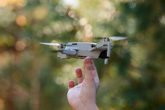 Drone quadrirotor sur la main de l'opérateur. un petit drone atterrit à portée de main après avoir pris des vidéos et des photos. livraison d'air télécommandée et espion.