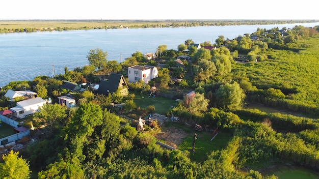 Drone survolent la rivière ondulante de couleur bleue entourée d'un village local avec divers bâtiments