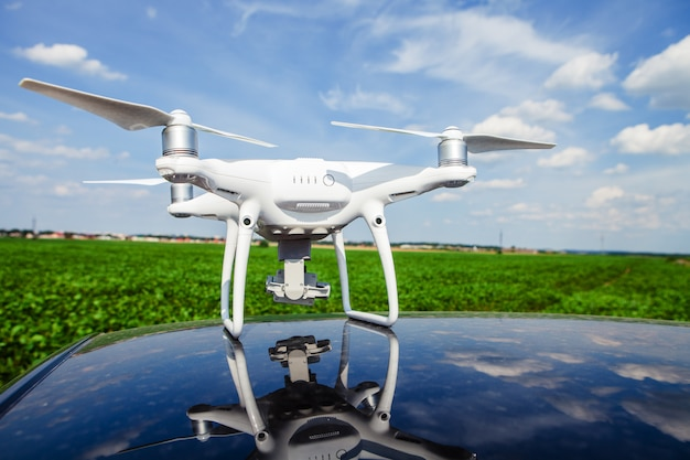 Drone sur le toit de la voiture sur un fond le champ vert