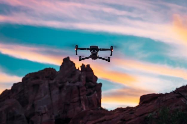 Drone volant au coucher du soleil, avec fond montagneux