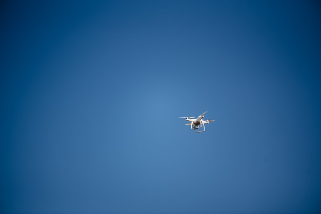Drone volant de quad copter dans un ciel bleu clair