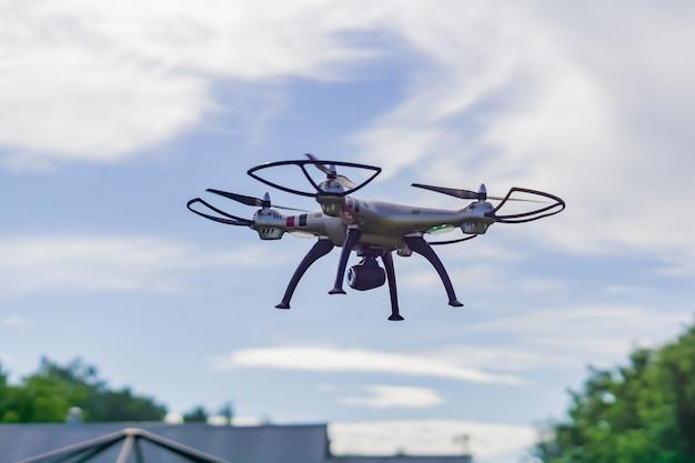Drone volant avec télécommande sur fond de ciel bleu.