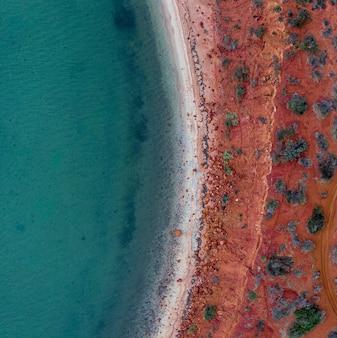 Drone vue sur la mer entourée par le rivage recouvert de sable rouge et de pierres