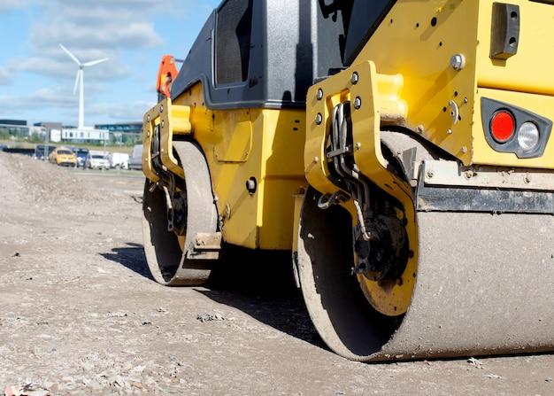 Drum ride on roller compactant le tarmac fraîchement posé pendant les travaux routiers et la construction d'un nouveau sentier