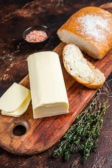 Du beurre à tartiner et des toasts alimentaires sur une planche à découper en bois. fond sombre. vue de dessus.