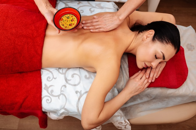Du bol coloré. une femme aux cheveux noirs paisible se refroidissant sur le ventre pendant que le maître soigne son dos