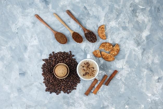 Du café avec des biscuits, des grains de café, du café moulu, des bâtons de cannelle dans une tasse sur fond gris grungy, vue du dessus.