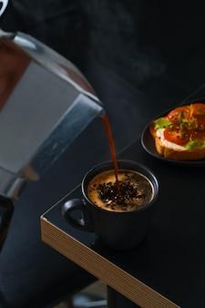 Du café expresso frais et chaud est versé dans une tasse à partir d'une cafetière geyser. table de bar, idée de petit-déjeuner au café, toasts au fromage et aux tomates ou antipasti.