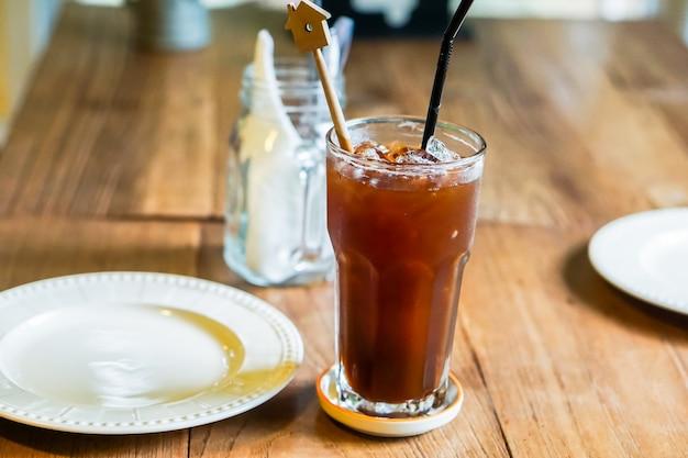 Du café glacé et un plat sont placés sur une table en bois.