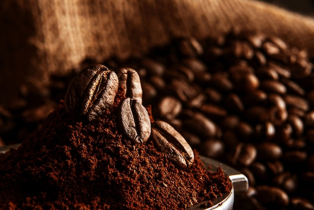 Du café moulu est versé dans le support sur lequel reposent les grains de café torréfié et parfumé. sur le fond des grains frits