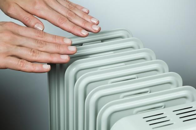 Du froid. chauffage par batteries. les mains sur le radiateur.