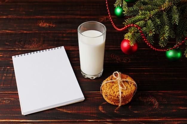 Du lait, des biscuits et une liste de souhaits sous le sapin de noël. le de l'arrivée du père noël.
