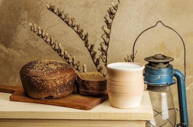 Du lait dans un pot en céramique, du pain de seigle et une lanterne à pétrole. nature morte au style rustique