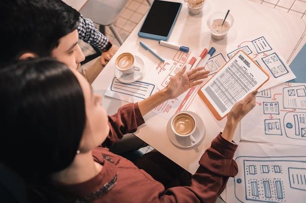 Du matin. deux hommes d'affaires réussis créatifs intelligents travaillant et buvant du café le matin