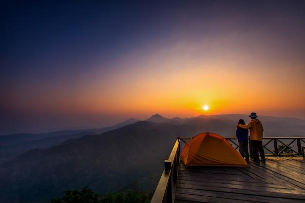 Du matin. les touristes regardent le lever du soleil sur un balcon en bois.